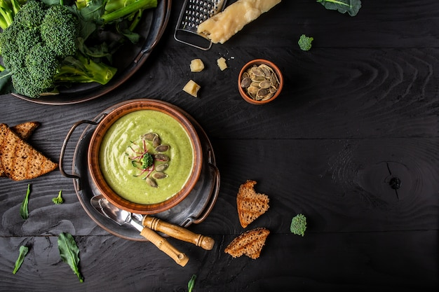 Broccoli soup puree with parmesan and crispy croutons on a dark wood background