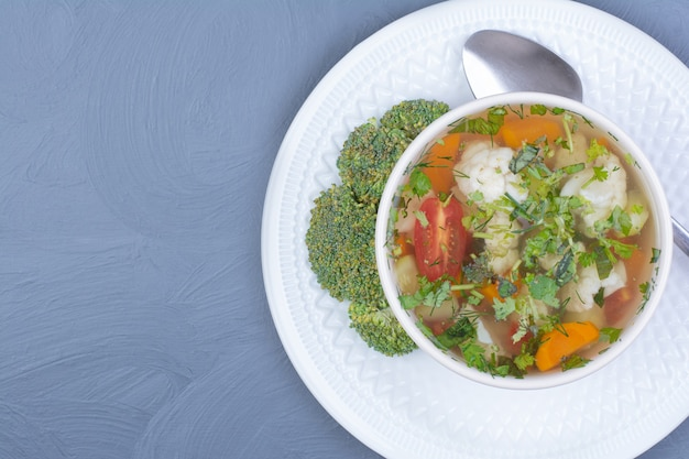 Broccoli soup with vegetables and herbs in a white cup.