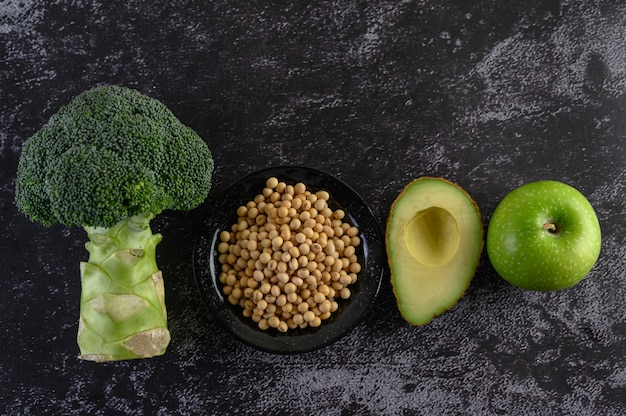 Broccoli, soy beans, apple, and avocado on a black cement floor.