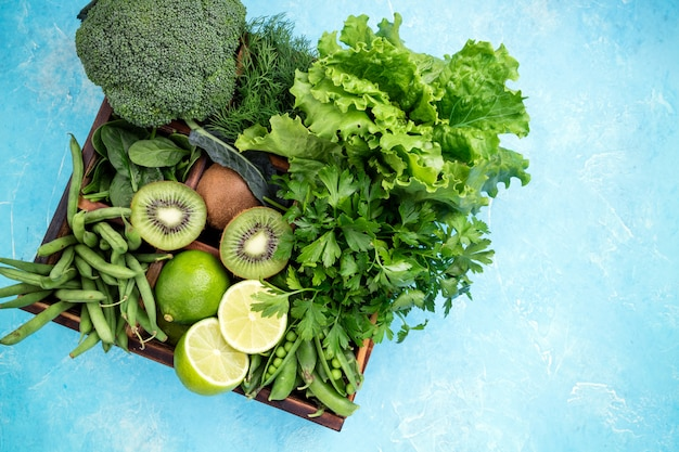 Broccoli, spinach, kiwi, lettuce, parsley, dill, asparagus beans, lime on blue background
