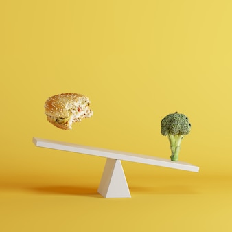 Broccoli vegetable tipping seesaw with floating berger on opposite end on yellow background.
