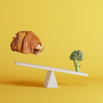 Broccoli vegetable tipping seesaw with floating pork leg on opposite end on yellow background.