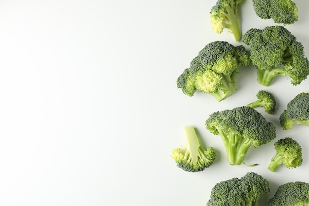 Broccoli on white surface and space for text