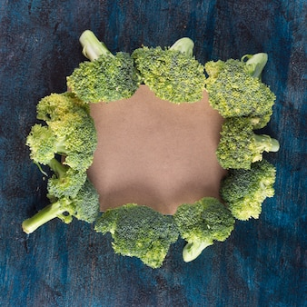 Broccoli with blank paper on table