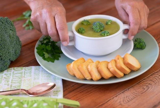 ブロッコリー。ブロッコリーのグリーンクリームスープとクルトンを持った女性の手で、カロリーはなくビタミンを使った健康的な食事を楽しめます。健康的な栄養の概念