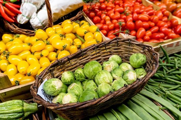 地元のファーマーズマーケットのバスケットに入ったブロッコリー、ズッキーニ、インゲン、芽キャベツ、赤いトマト。