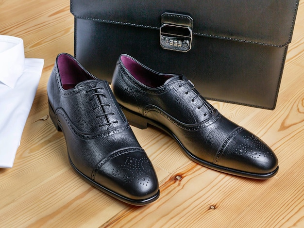 Brogues in black leather on a background of light boards. nearby is a business briefcase and a shirt. selective focus, close-up