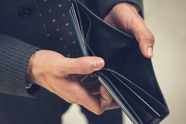 Broke businessman opening empty wallet