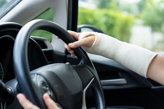 車を運転して腕の骨折した女性。安全運転のコンセプト。