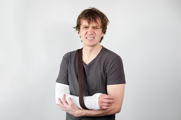 Broken arm. young unhappy caucasian man with plaster cast on his hand suffering from pain