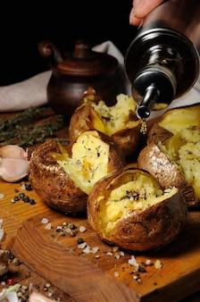 Картофель запеченный со специями и зеленью с добавлением масла на деревянной доске