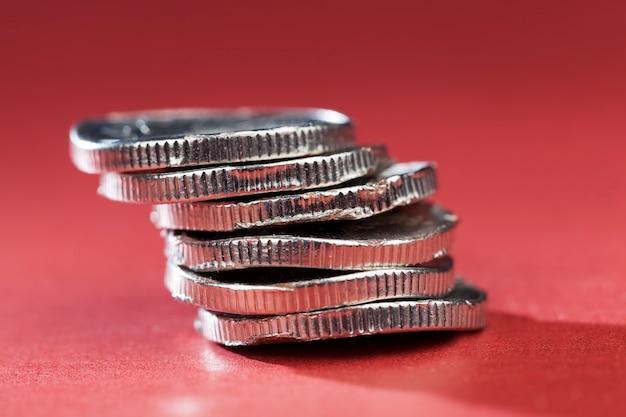 Сломанные изогнутые и ржавые металлические монеты на красном фоне