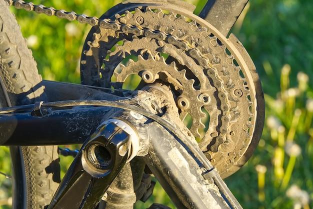 Сломанный велосипед, который нуждается в ремонте, лежит на зеленой траве, пока его педали сняты.