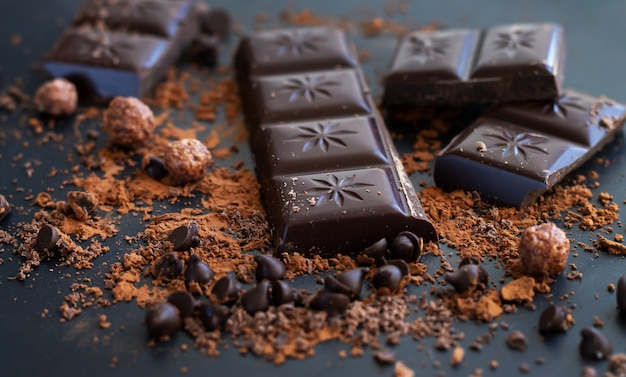 Разбитые кусочки плитки горького шоколада и какао-порошок на темной поверхности