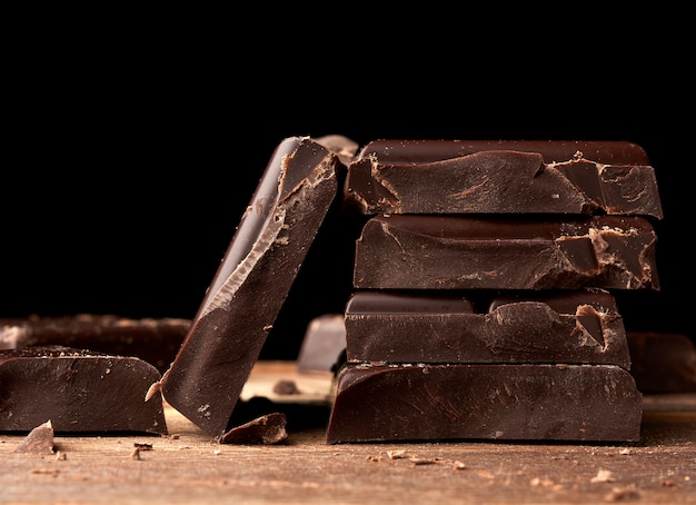 Broken black chocolate on a wooden table, culinary sweet ingredient