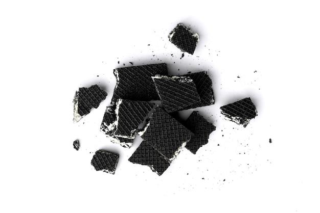 Сломанные черные вафли, изолированные на белом фоне.