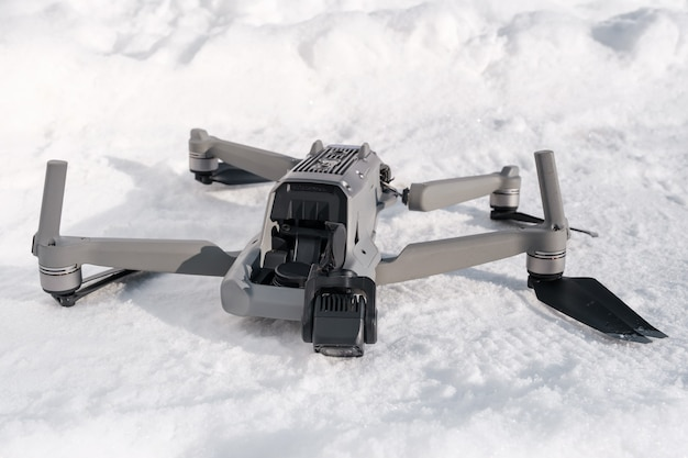 Broken camera and drone arm after crash on snow in winter
