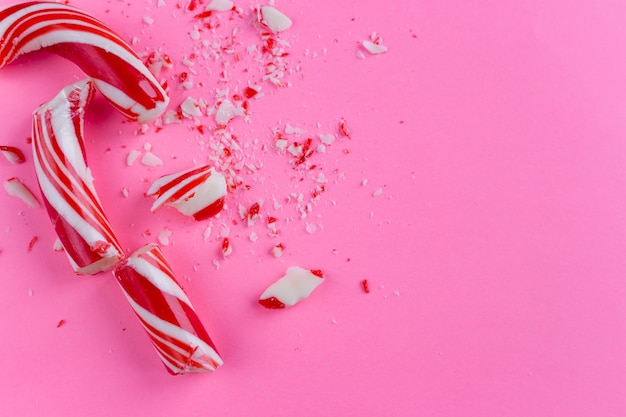 Broken candy cane on pink background. close-up photo