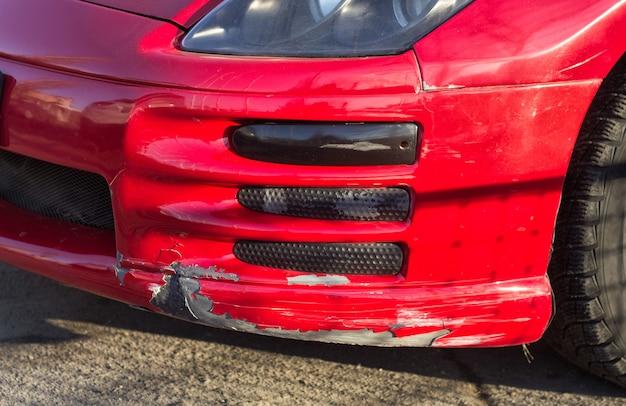 Сломанный автомобильный бампер красного спортивного автомобиля с заниженной подвеской