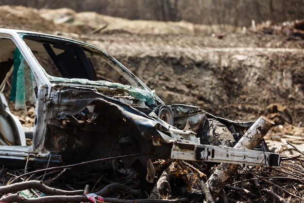 Broken car in a dump in the field