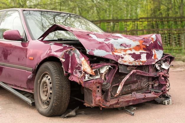 Разбитая машина. фиолетовая машина после аварии. ржавый бампер.