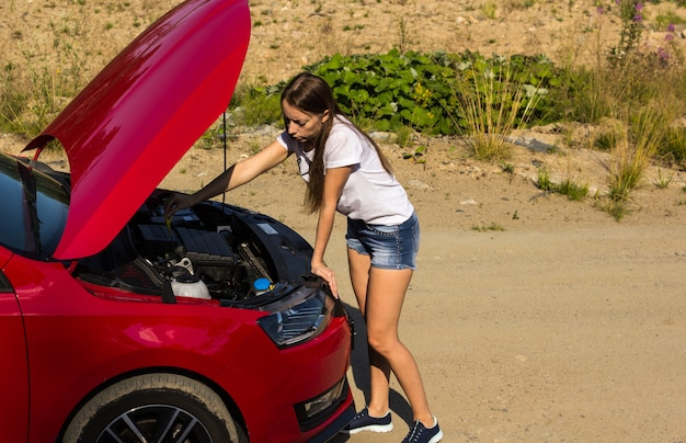 A broken car on the road, the girl checks the oil level