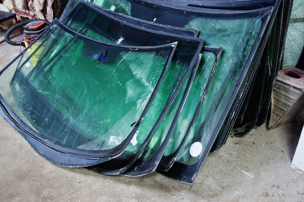 Broken car windshield, replacing windscreen of a car in auto service station garage.