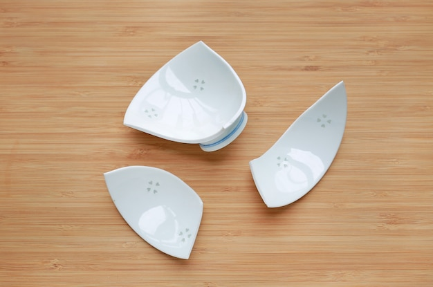 Broken ceramic bowl on wood background. top view.