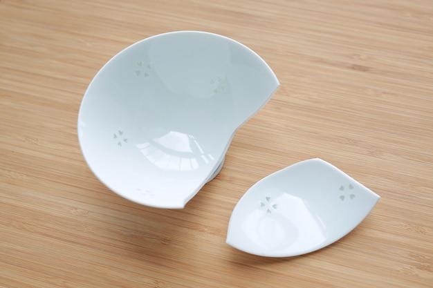 Broken ceramic bowl on wood background.
