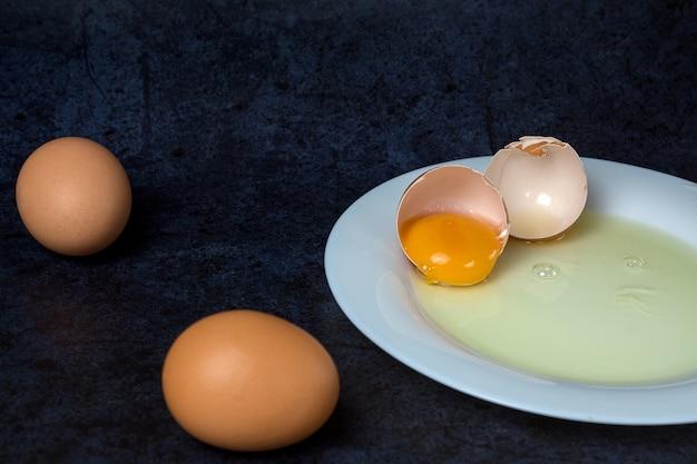 青のプレートで壊れた鶏の卵