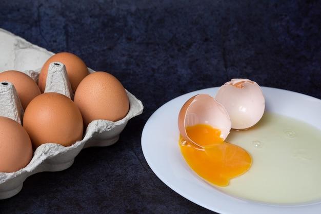 파란색 접시에 깨진 된 닭고기 달걀