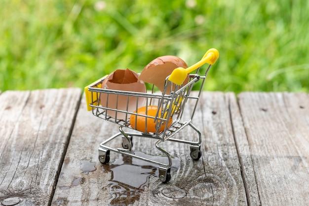 A broken chicken egg in a shopping cart.