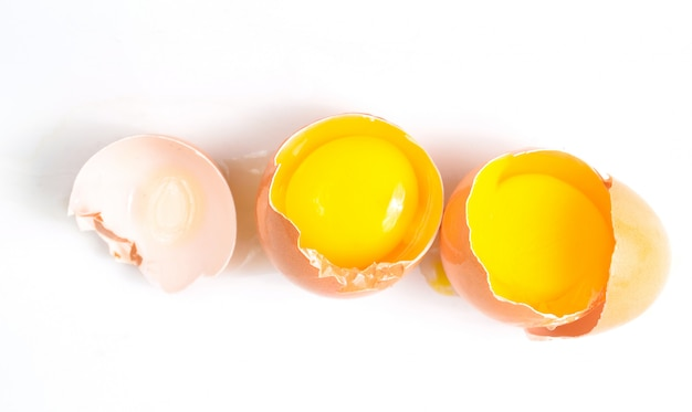 Broken chicken eggs isolated on white surface