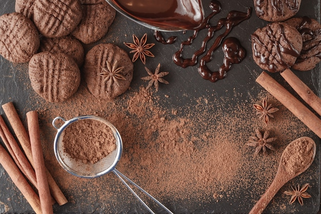 壊れたチョコレートバーと石のボード上のスパイス