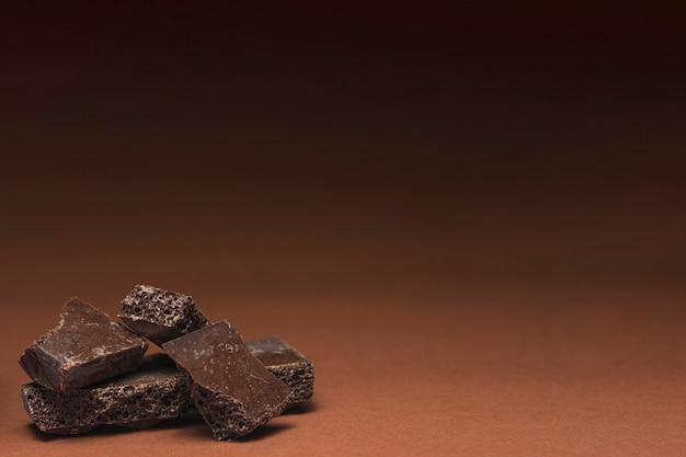 Broken chocolate bar on brown background