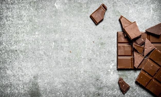 Сломанная плитка шоколада на каменном столе