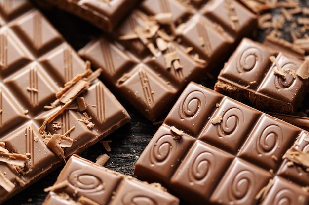 Сломанные плитки шоколада на черном.