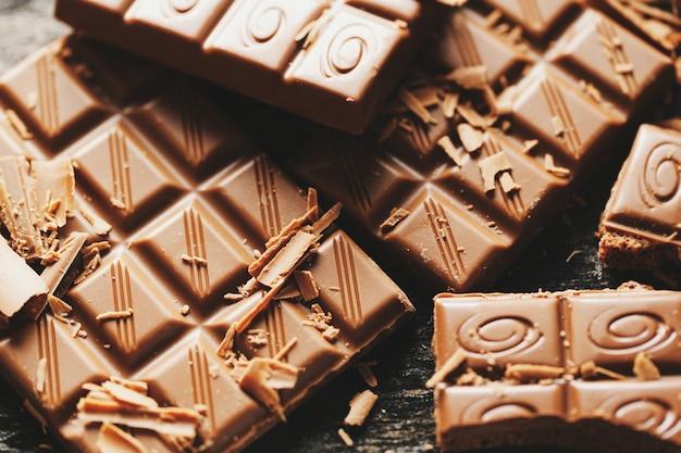 Сломанные плитки шоколада на темном фоне. крупный план. шоколадный фон. крупным планом