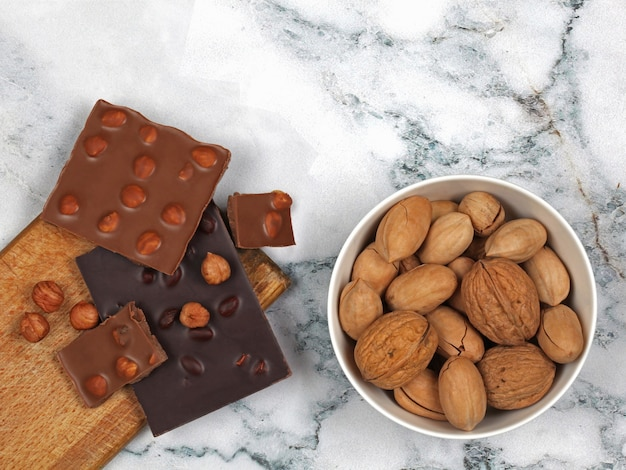 Broken chocolate bars and raw nuts on gray marble background. top view with copy space