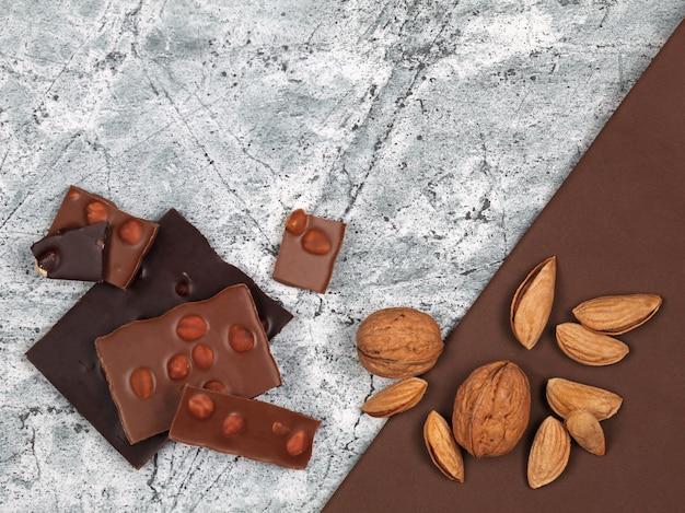 灰色の石の背景に壊れたチョコレートバー、クルミ、アーモンド。コピースペースのある上面図