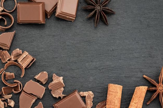 Разбитые кусочки шоколада и шоколадная стружка на темном фоне. вид сверху с copyspace для вашего текста.