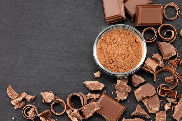 Сломанные кусочки шоколада и какао-порошок на темном фоне. вид сверху с copyspace для вашего текста.