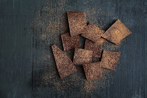 Broken chocolate pieces and cocoa powder on black background. copy space.