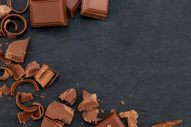 Broken chocolate pieces and cocoa powder on a dark.