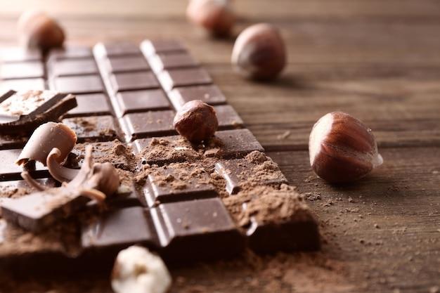 木製のテーブルに壊れたチョコレートのかけら、ナッツ、ココアケーキ