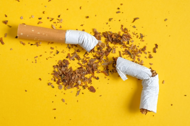 Broken cigarette in half with a row of scattered tobacco on yellow