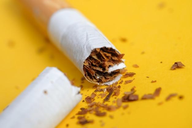 Broken cigarette in half on yellow