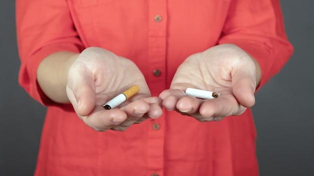 女性の手で壊れたタバコ、禁煙サイン。