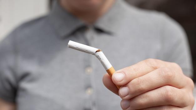 Сломанная сигарета в руке крупным планом. вредная привычка, бросить курить, вред от курения табака и никотина, концепция здоровья