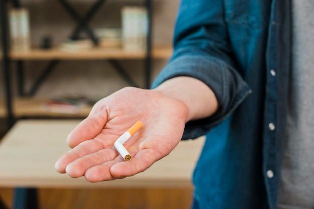 남자의 손에서 부러진 된 담배